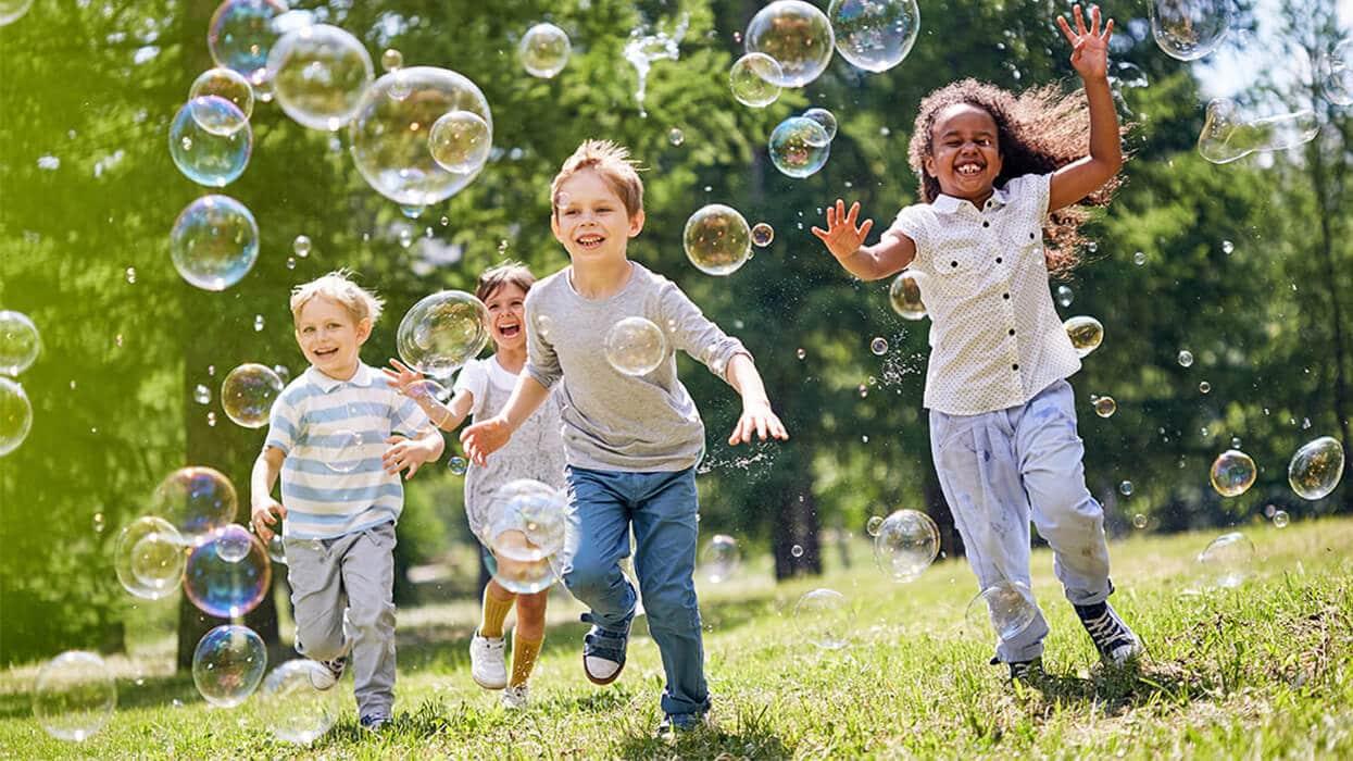 Kinder im Park mit Seifenblasen