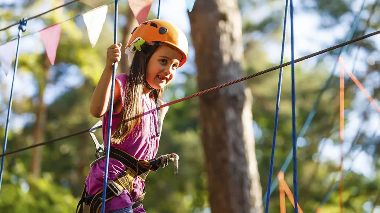 Kleines Mädchen klettert im Wald